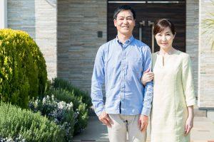 玄関の前で腕を組んで並ぶ夫婦