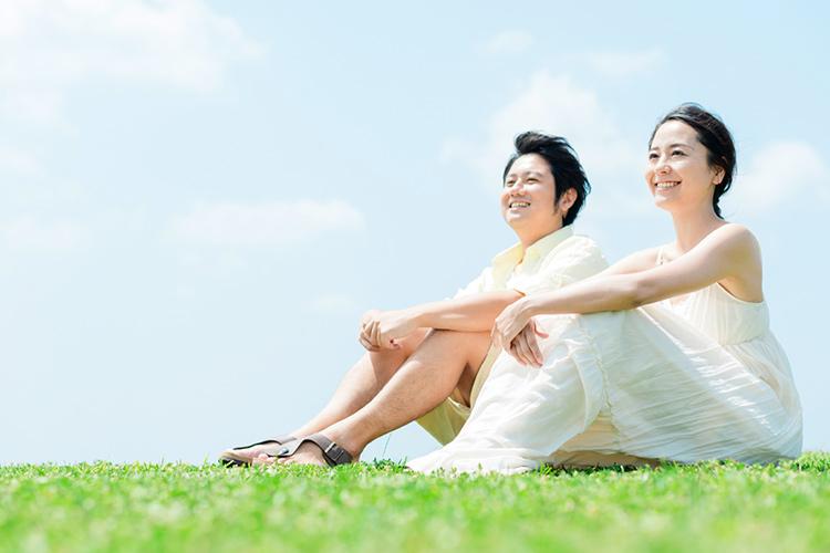 青空の下芝生に並んで座る男女